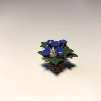 Blå blomster i flet urtepotte